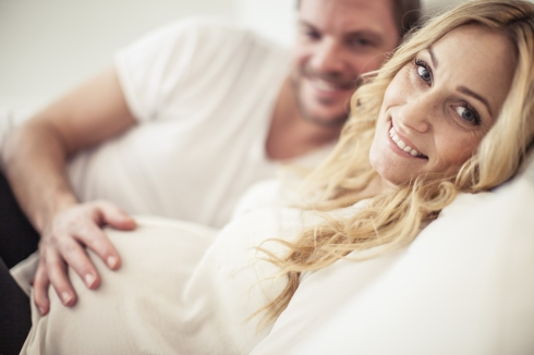 portrait-of-happy-pregnant-woman-with-man-lying-in-bed-1